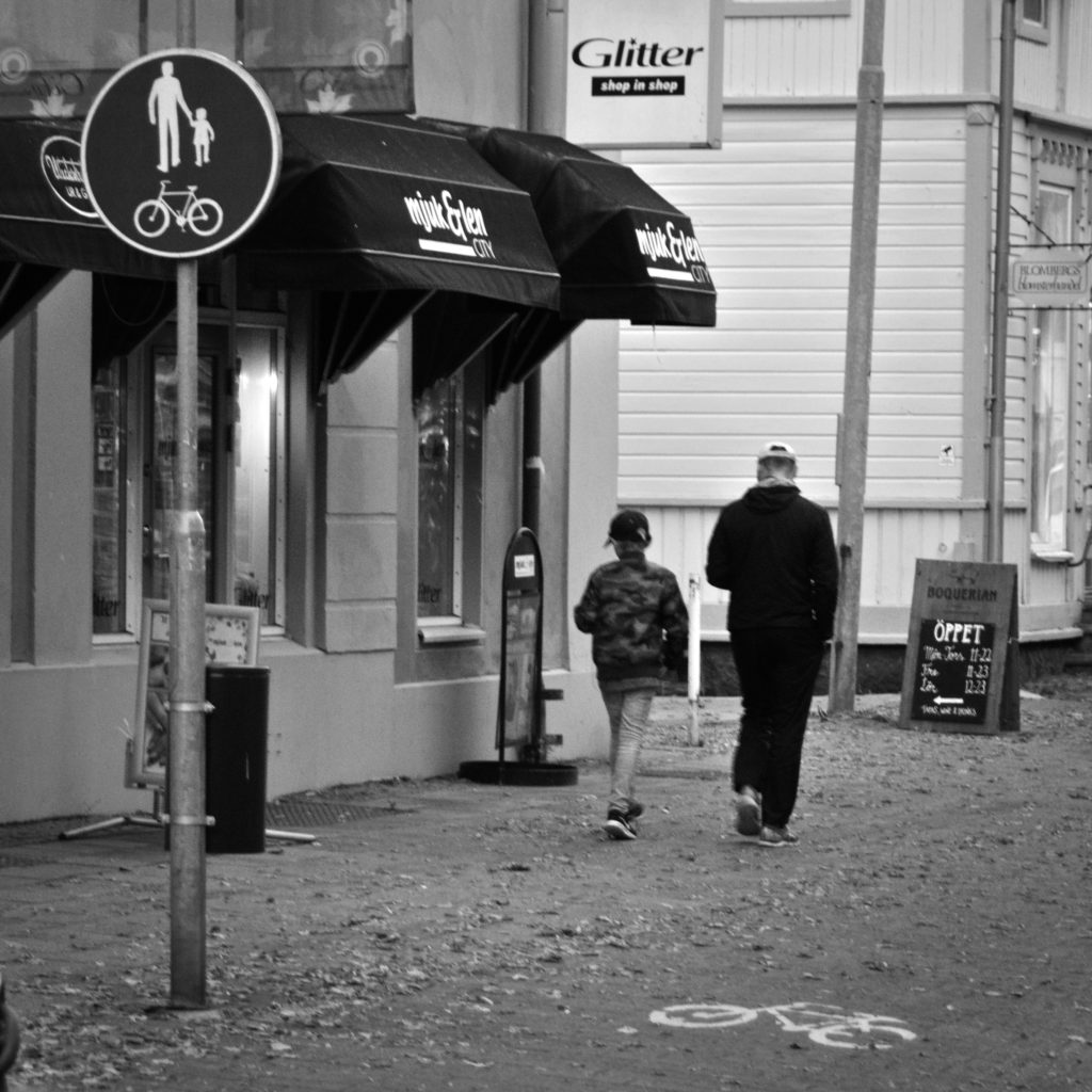 A street photography session in Mariehamn with a boy and maybe a father walking on the pavement.