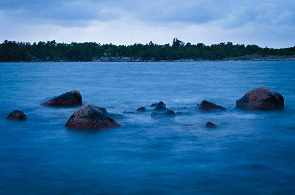Dorsholm med stenar i vattnet som förgrund utanför Västra Simskäla på Åland.