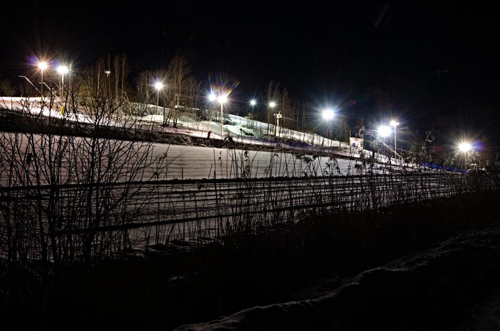 Germundö Alpin sedd från parkeringen i mörker med belysningen tänd över nedfarterna, Åland.