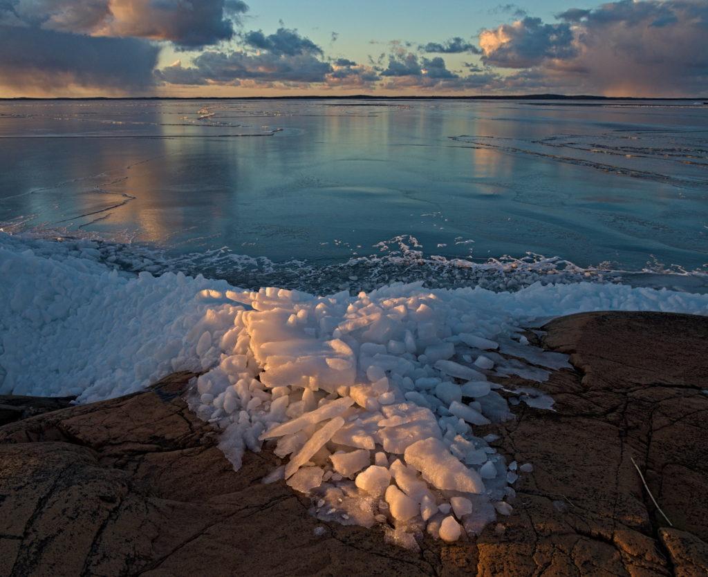 Sista kvällsljuset lyser över krossad is på Lumparns strand i mars. Åland.