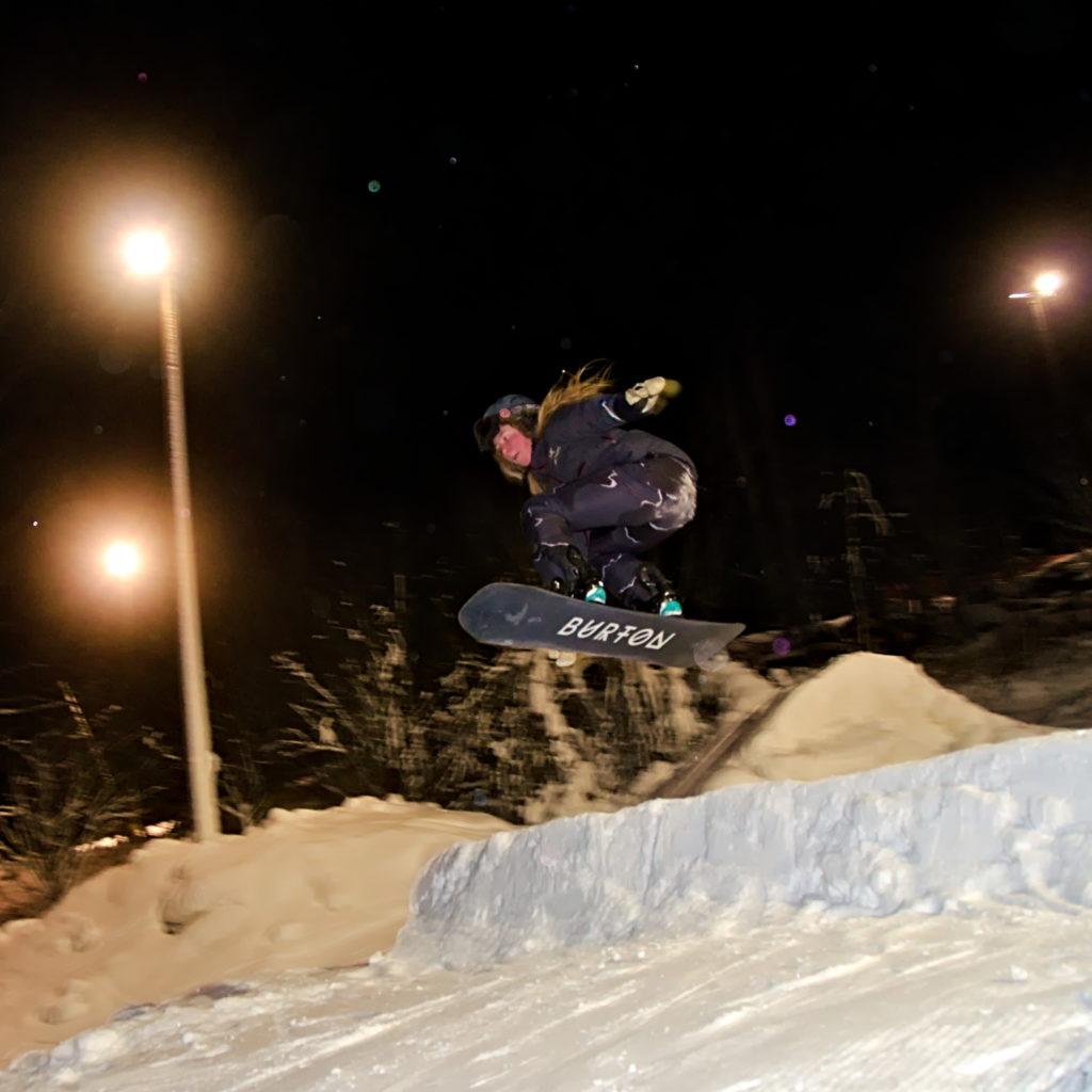 Malva Lomner gör en grab med snowboard i hoppet på Germundö Alpin, Åland.