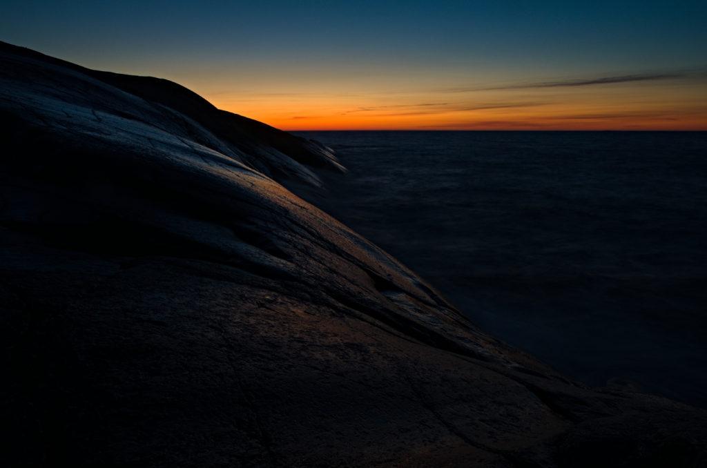 Solens sista strålar över klipporna i Geta med Norrhavet som ridå. Åland.